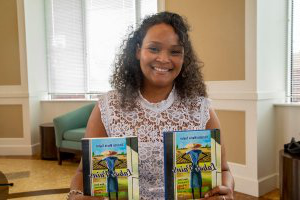 "AG老虎机 Assistant Professor of English Christin Taylor, Ph.D., with her book ""Labor Pains."""
